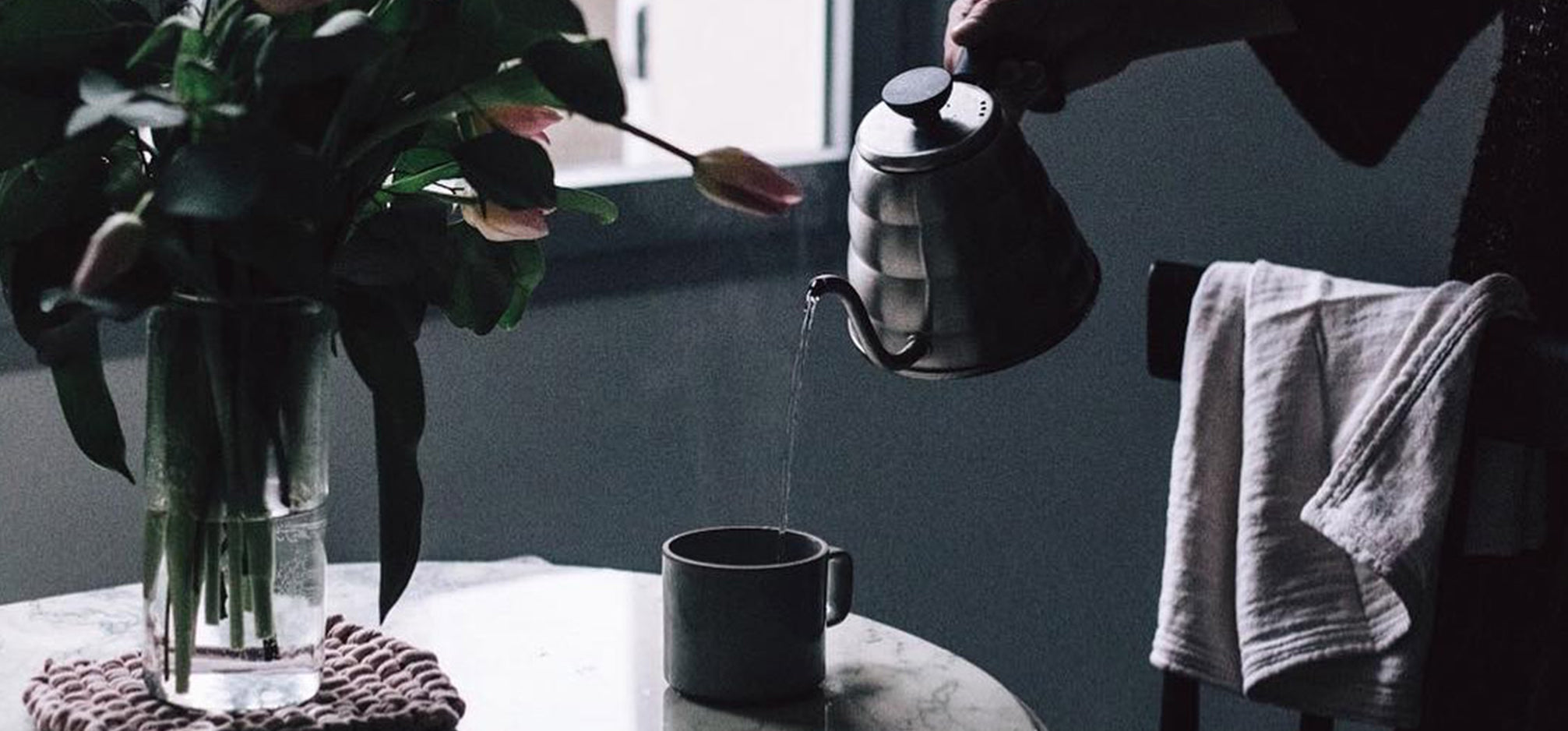 Someone pouring a kettle into a mug next to a bouquet of tulips.