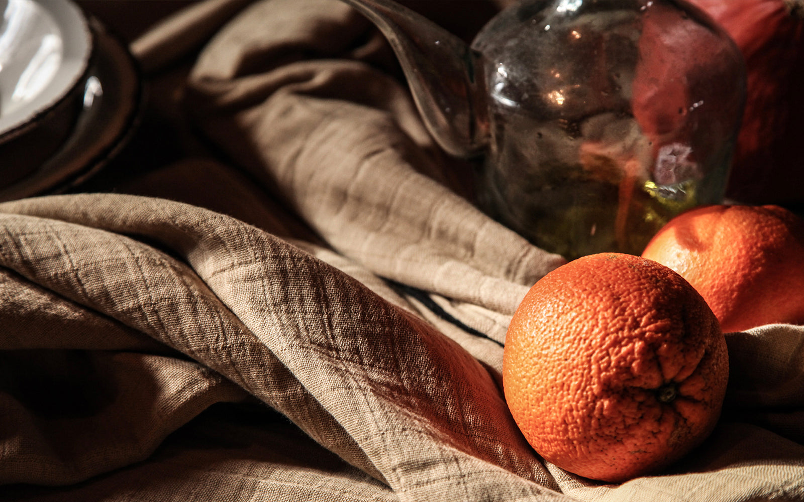 Light brown textured gauze cotton tablecloth with some oranges and a glass teapot on it.