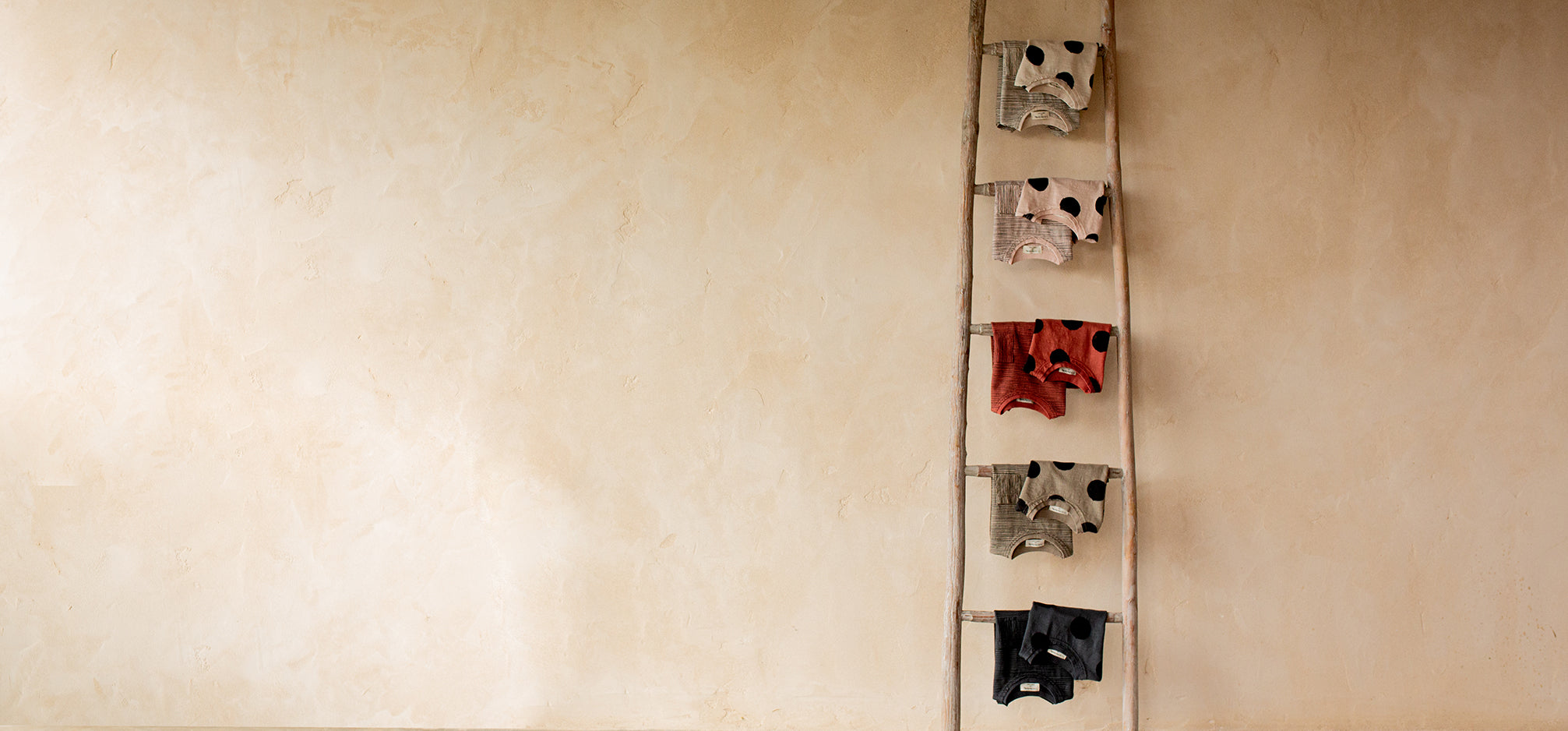 Folded baby clothing hanging from a wooden ladder leaning against a beige wall.