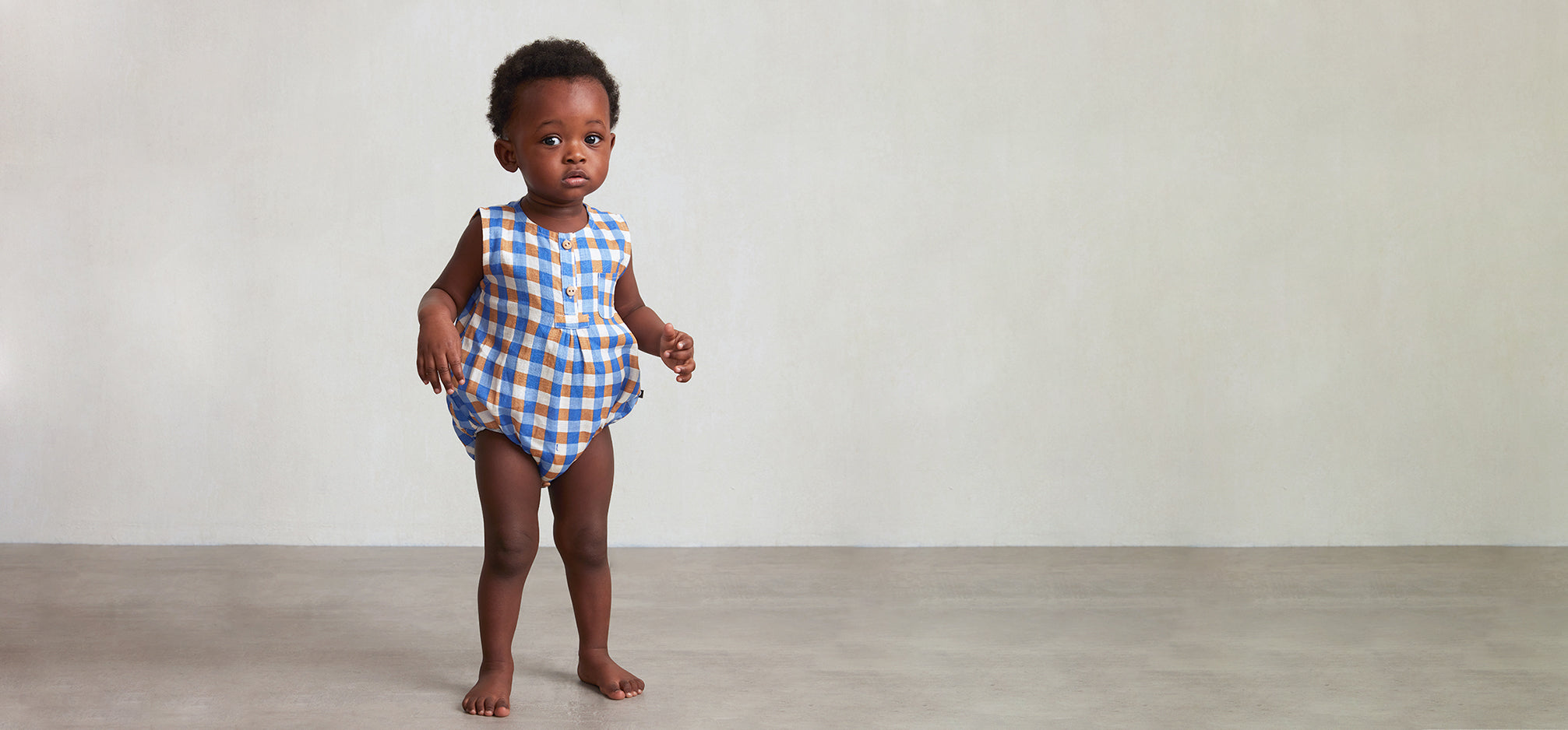Baby standing wearing a blue gingham romper.