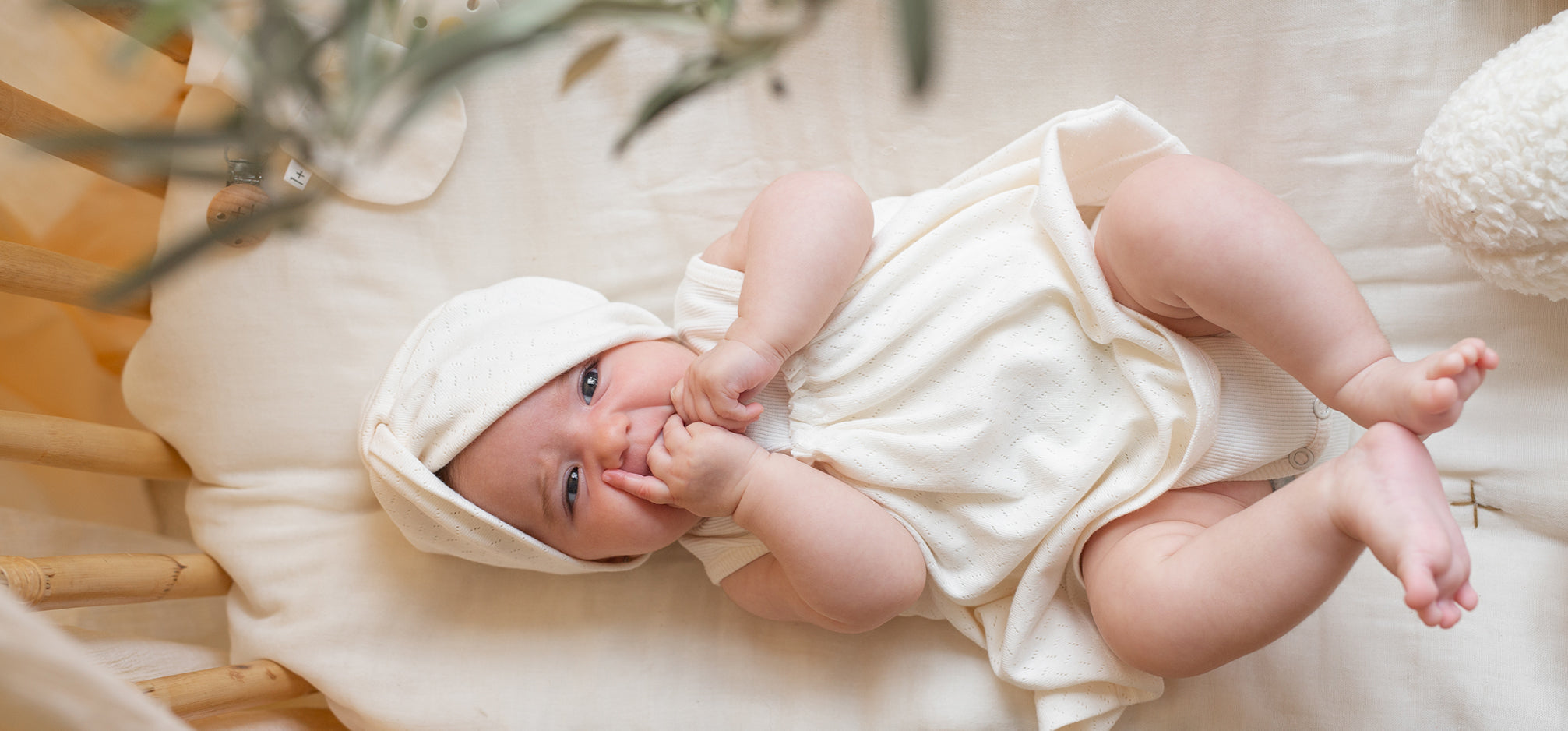 A baby laying in a crib wearing a cream dress and matching bonnet.