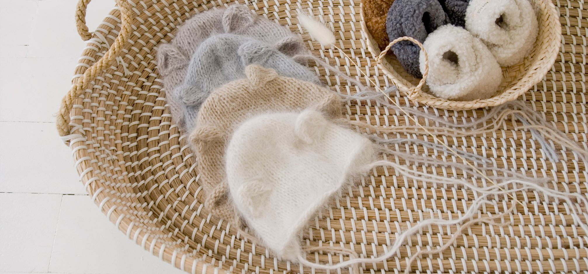 Knit baby bonnets and booties in a seagrass changing basket.