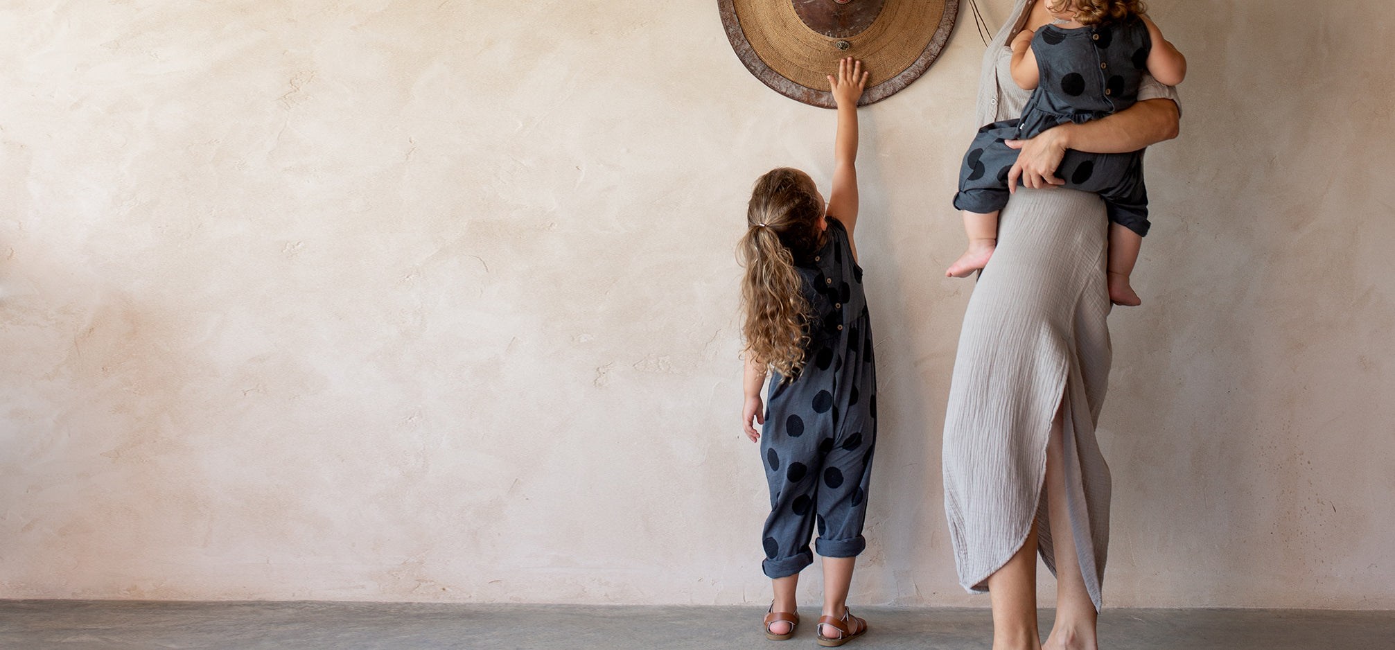 A mother holding a baby next to a girl reaching for some hats hanging on a wall.