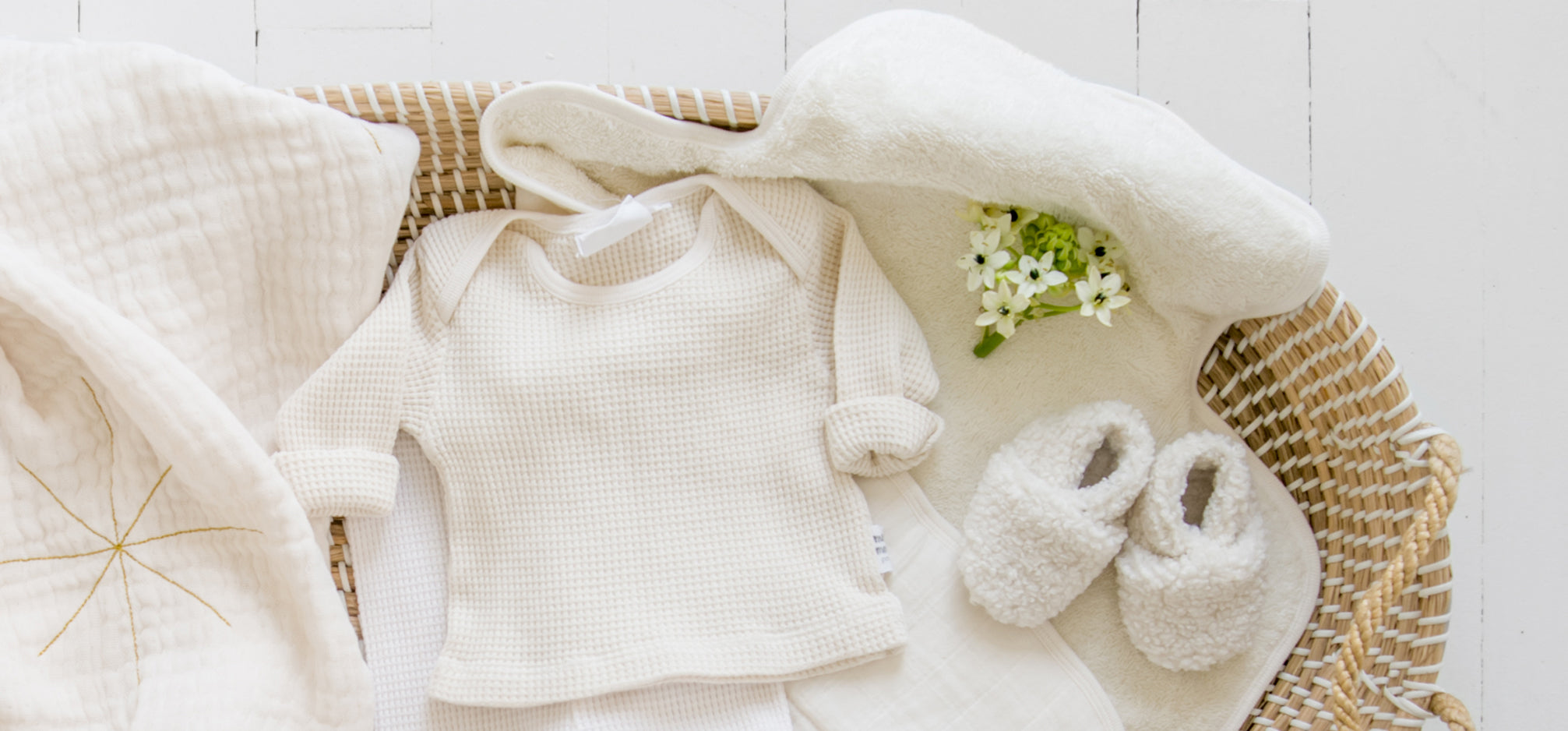 A cream baby outfit and blanket in a seagrass basket.