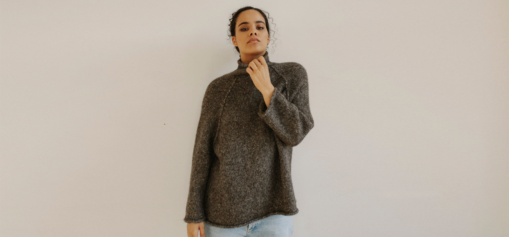 Woman with her hand on her chin wearing a funnel neck brown sweater.