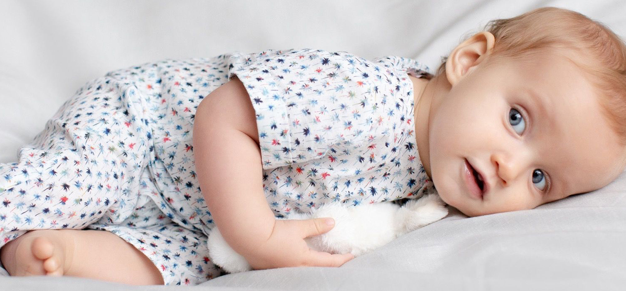 Baby laying down wearing a white cotton jumpsuit with an all over blue palm tree print.