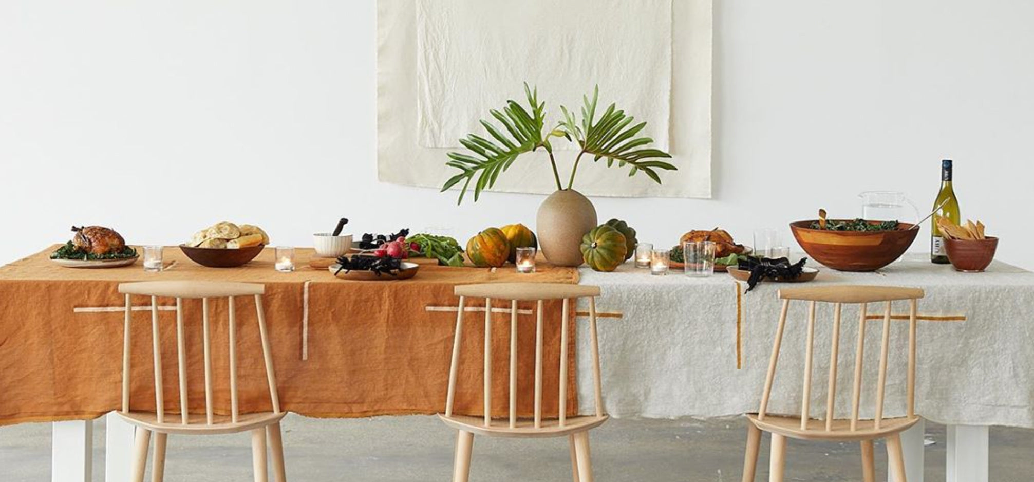 A beautifully arranged dinner table with rust orange linens.