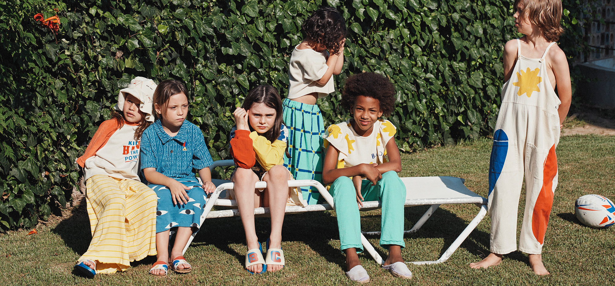Children sitting outside on a lawn chair.
