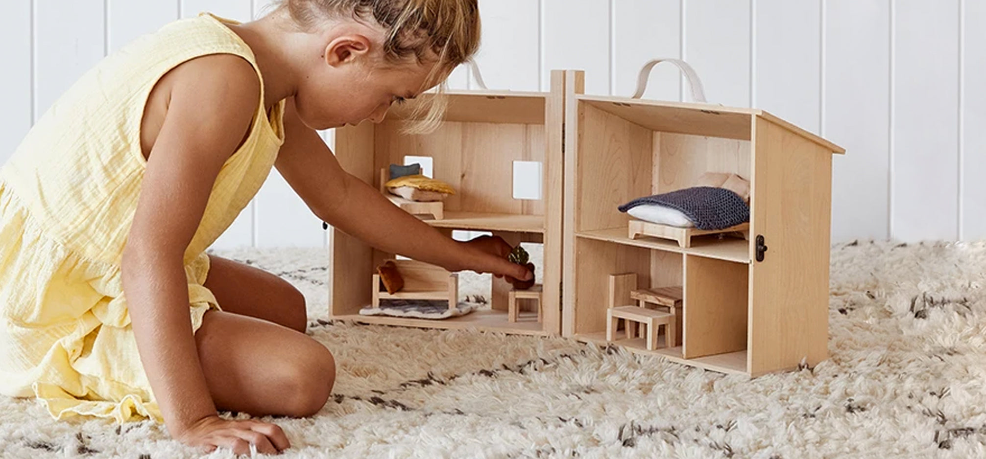 A girl playing with a wooden doll house.