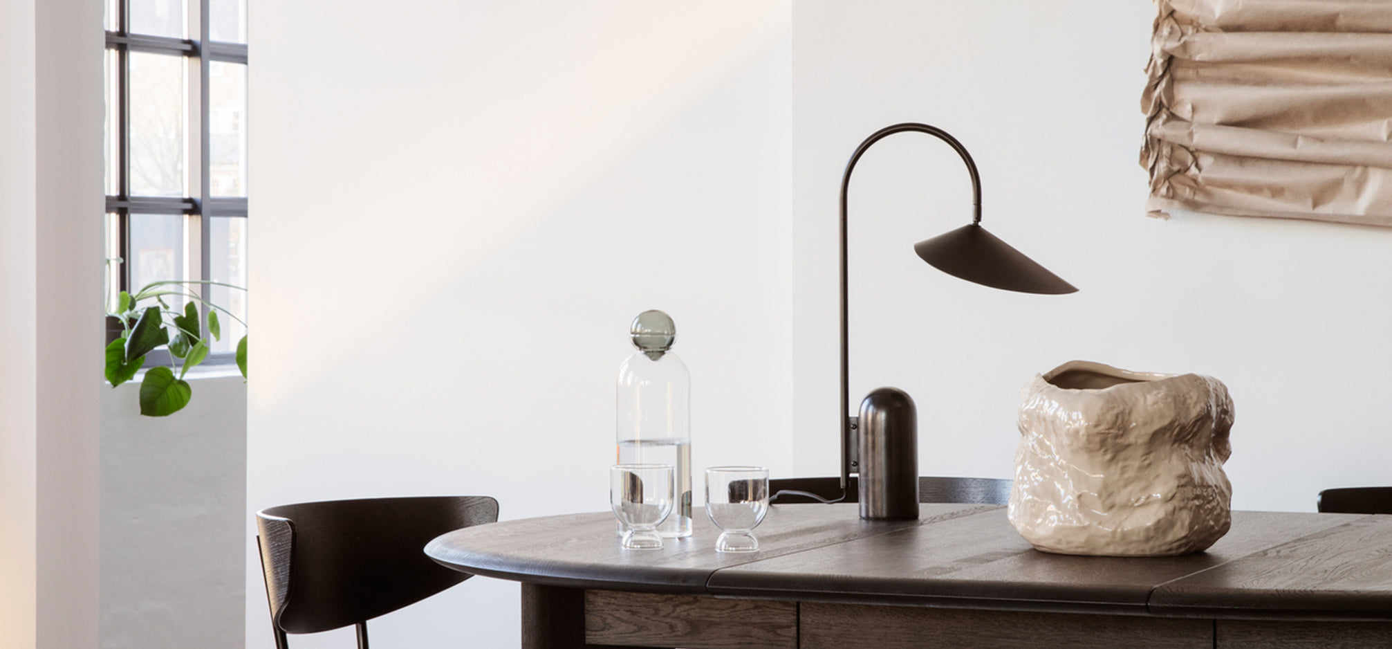 A dining table with a pitcher, lamp and vase on top.