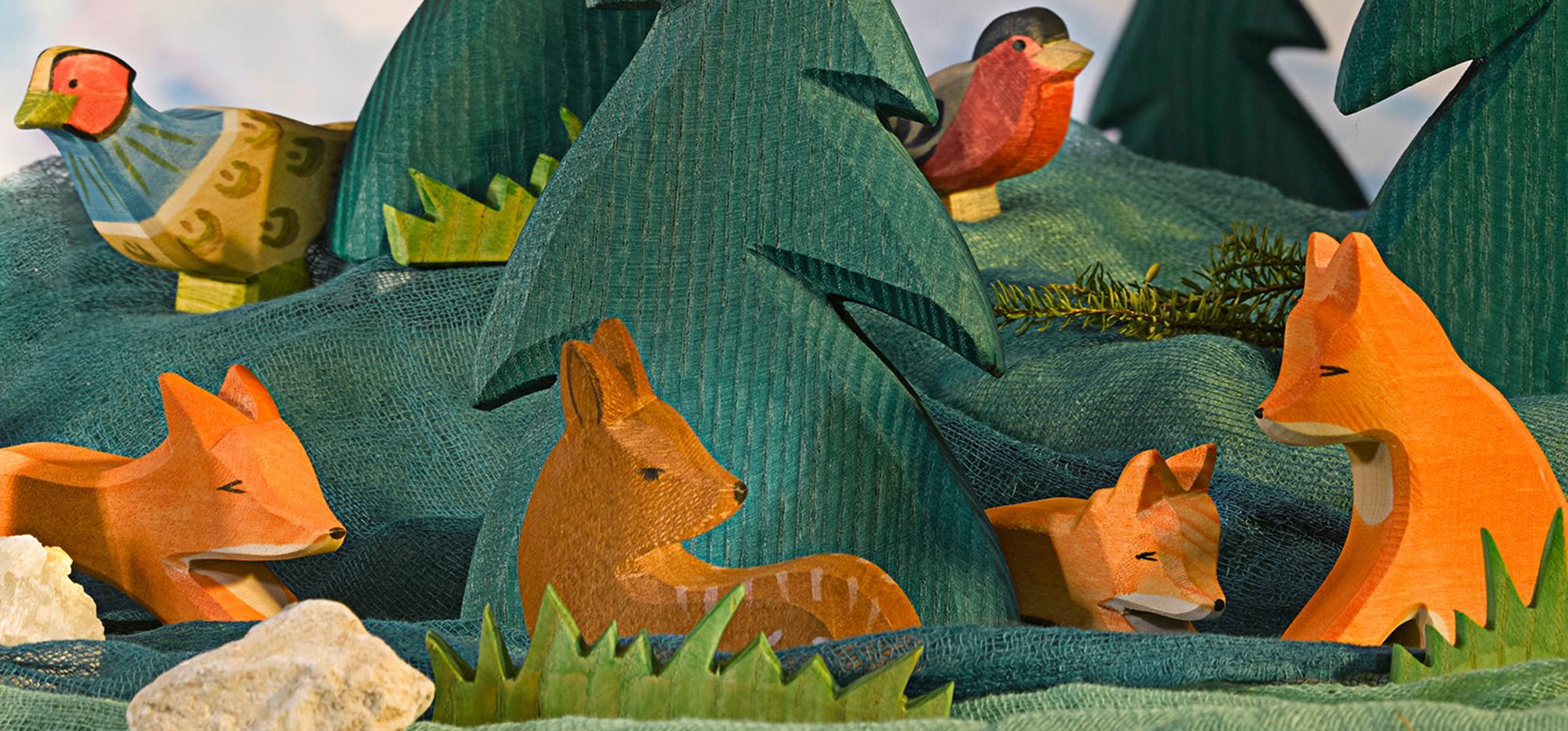 Carved and painted wooden animal figurines and trees.
