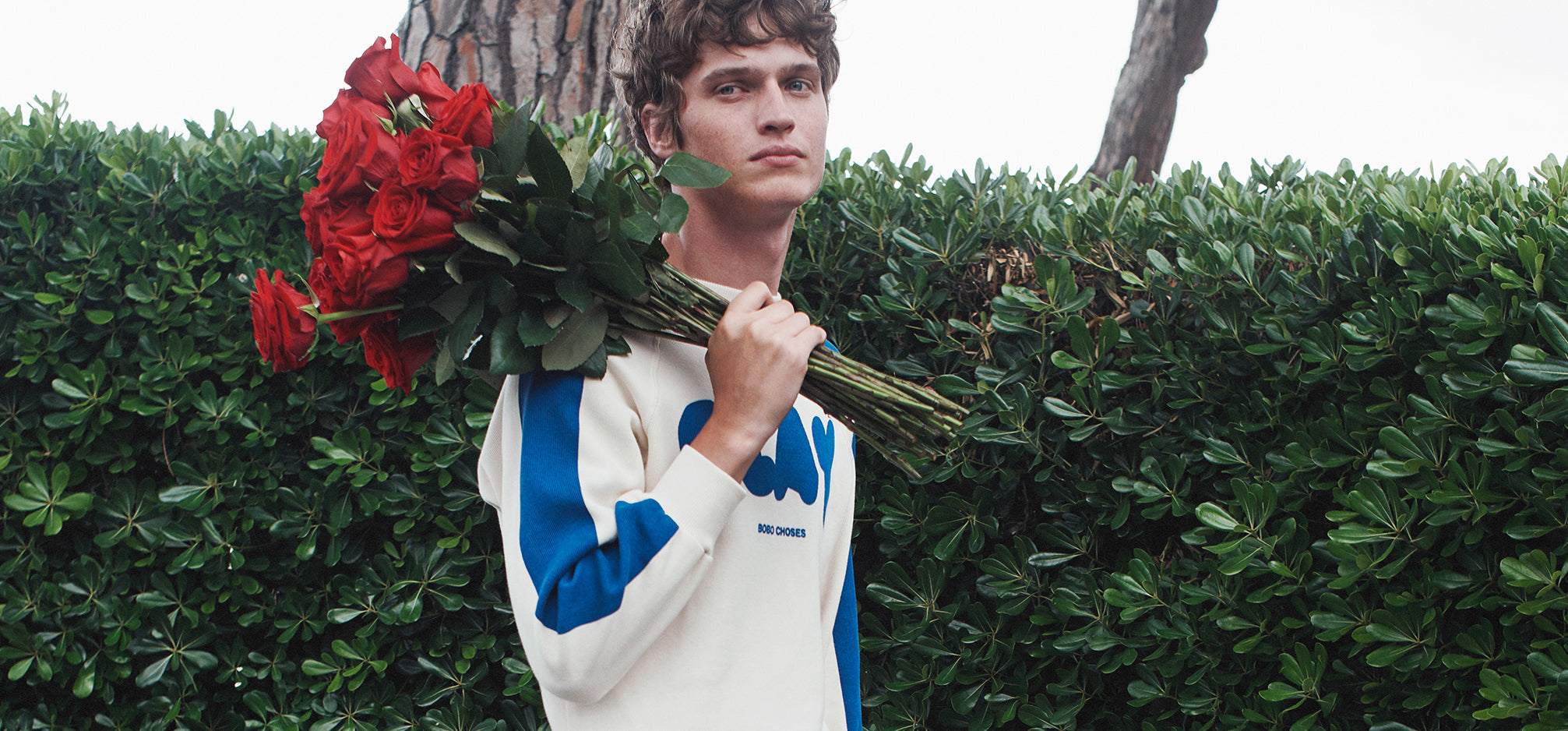 A man holding a bouquet of roses over his shoulder.