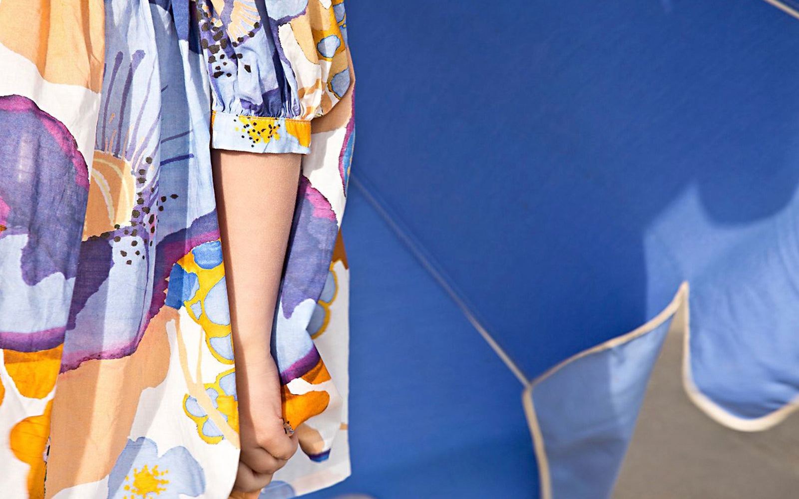 Close up of a girl wearing a floral printed dress in front of a large blue sun umbrella.