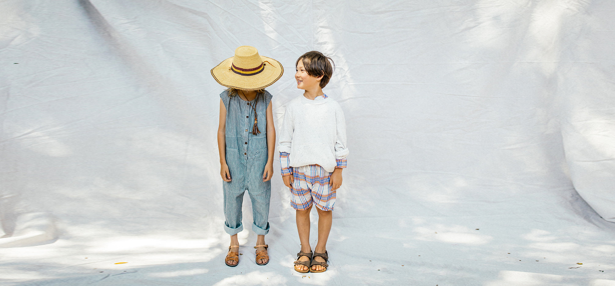 Two children standing in front of a white backdrop.