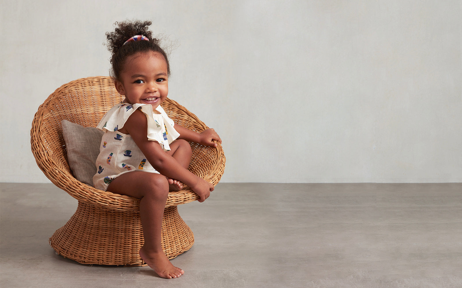 Toddler sitting in a rattan chair wearing a cute patterned romper.