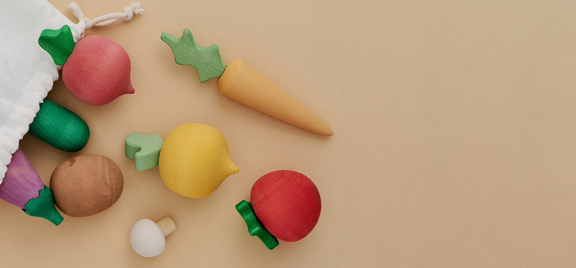 Painted wooden fruit toys coming out of a cloth bag.