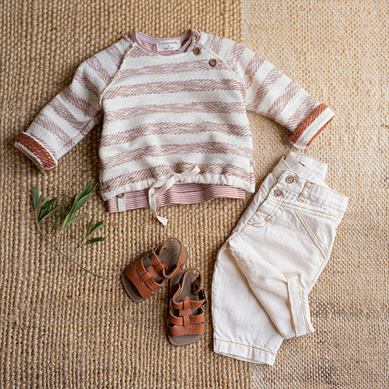 Baby outfit including a cream and red striped sweater, white pants and brown sandals on a jute rug.
