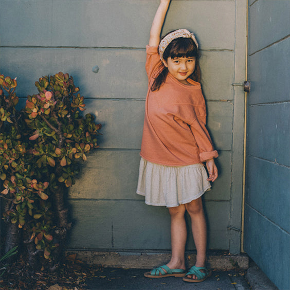 Girl standing in front of a blue wall and bush wearing a rust red sweatshirt and skirt.