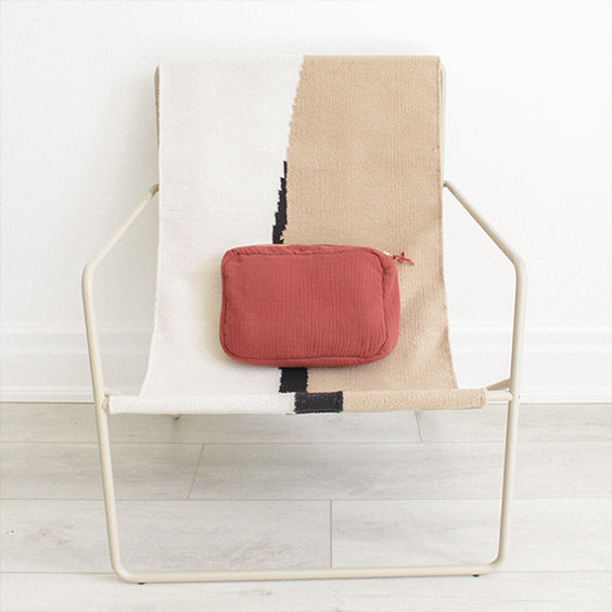 Red brown zippered pouch on a woven canvas chair with a cream metal frame.