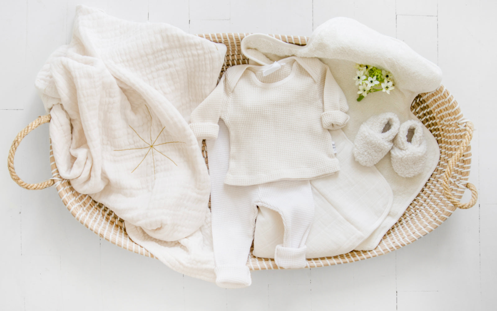 Cream coloured baby outfit and swaddle blanket in a woven changing basket.