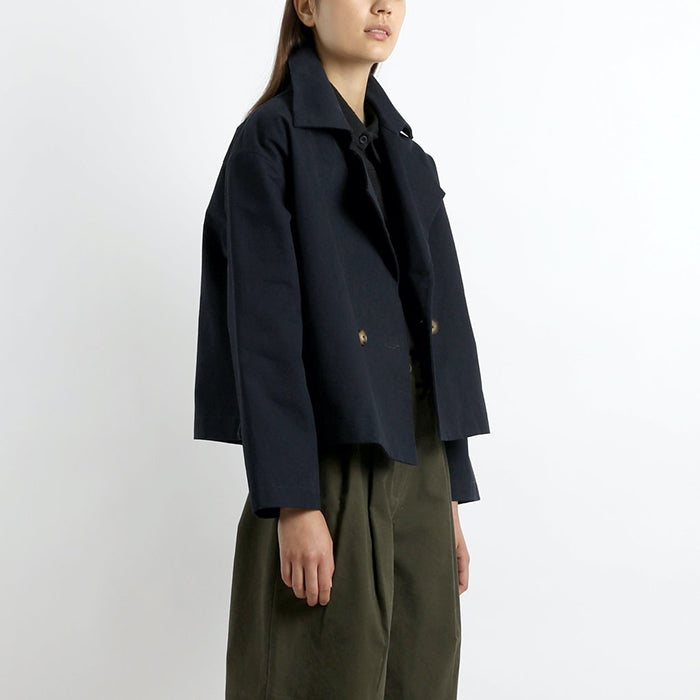 Woman wearing a cropped peacoat in navy blue.