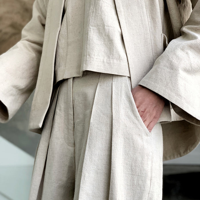 Woman descending stairs wearing a beige linen canvas outfit including the pleated pants.