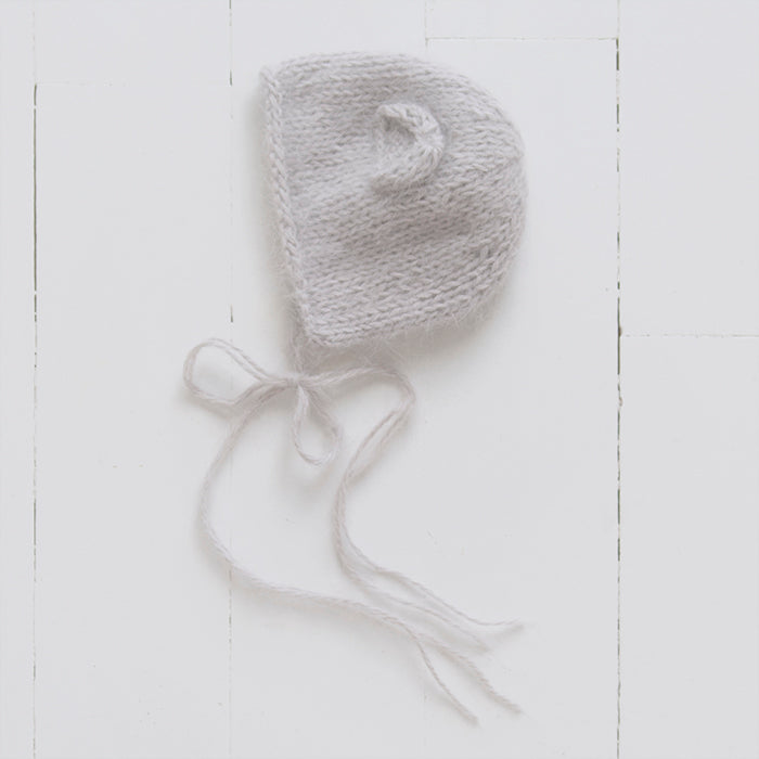 Hand knit baby bonnet with ears and long ties under the chin in a light taupe grey fluffy angora wool from the side.