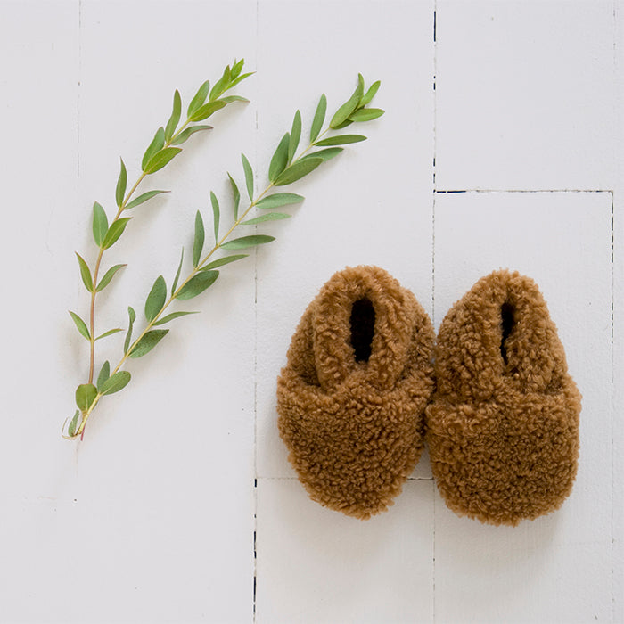 Pair of brown faux shearling baby booties next to some leaves.