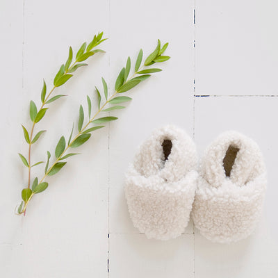 Pair of cream faux shearling baby booties next to some leaves.