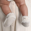 Baby being held wearing a pair of cream faux shearling baby booties.