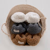 Basket holding three colours of faux shearling baby booties.