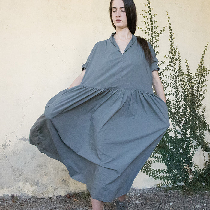 Woman standing wearing a grey short sleeved midi length dress with a gathered skirt.