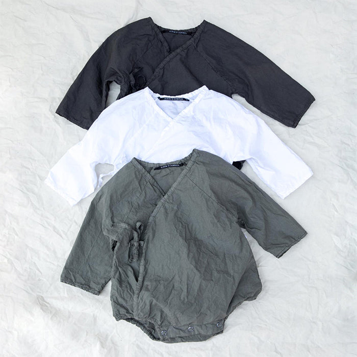 Three monochrome baby long sleeved rompers without legs.