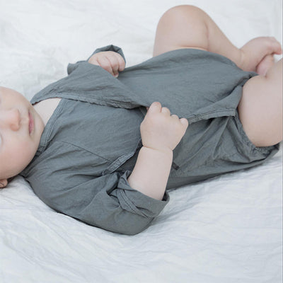 Baby laying down wearing a grey long sleeved romper from the side.