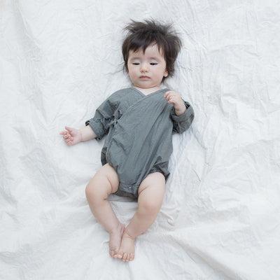 Baby laying down wearing a grey long sleeved romper from the top.