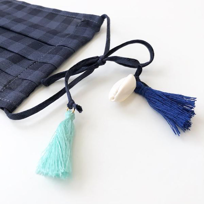 Gingham pleated face mask with blue tassel and shell details.