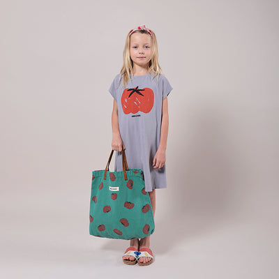 Girl standing wearing a short sleeved t-shirt dress in purple with a red illustrated tomato print on the front and holding a bag.