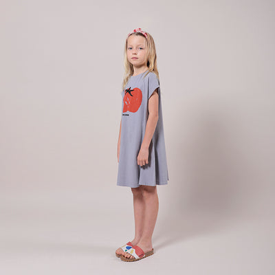 Girl standing wearing a short sleeved t-shirt dress in purple with a red illustrated tomato print on the front from the side.