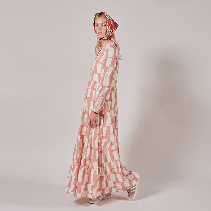Woman standing wearing a long sleeved maxi dress in pink with an all over white rectangle print from the side.
