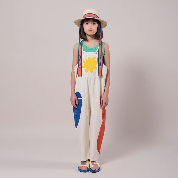 Girl standing wearing a white sleeveless overalls with abstract shapes print.