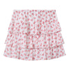 Short tiered skirt in white with an all over pink floral print on a textured Swiss dot cotton fabric from the back.