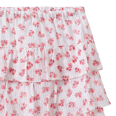 Close up of the tiered skirt in white with an all over pink floral print on a textured Swiss dot cotton fabric.