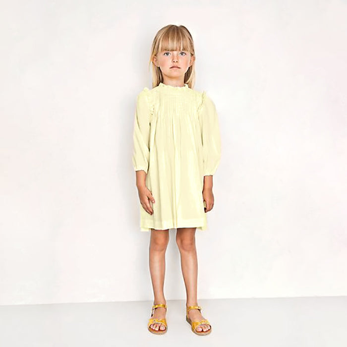 Pale yellow long sleeved dress with pleats across the chest and ruffles along the shoulder and neck.