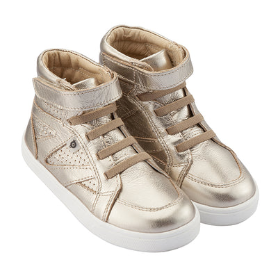 A pair of gold hightop sneakers with a velcro strap across the foot and perforated details from the side.