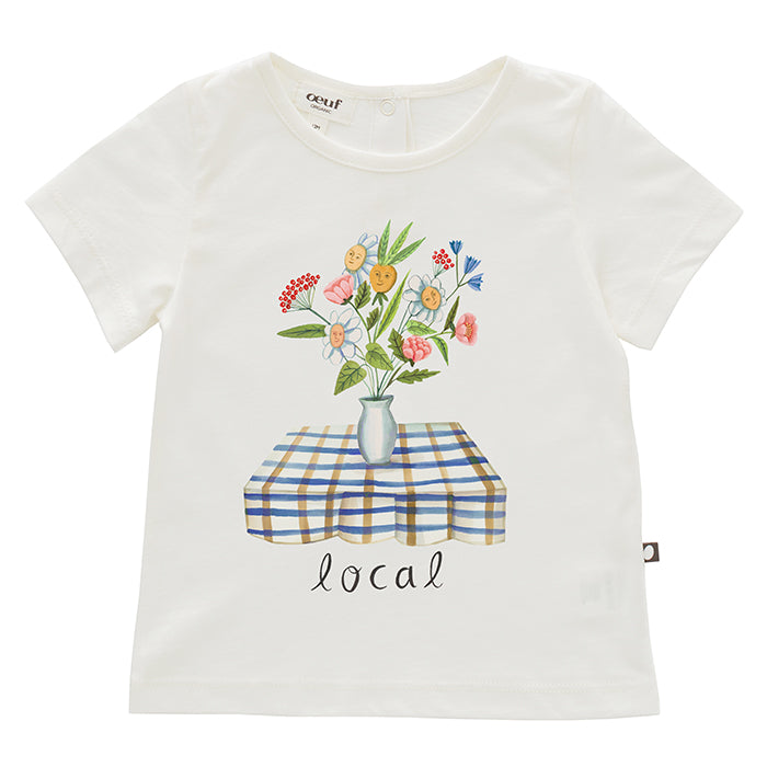 White short sleeved t-shirt with a cute print on the front of smiling flowers in a vase.