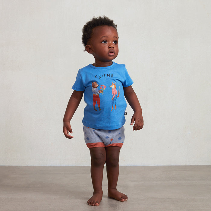 Baby standing wearing a blue short sleeved t-shirt.