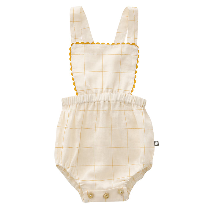 Baby girl from behind wearing Oeuf's overalls with a bib, thin straps, and no legs in cream with thin yellow checks.