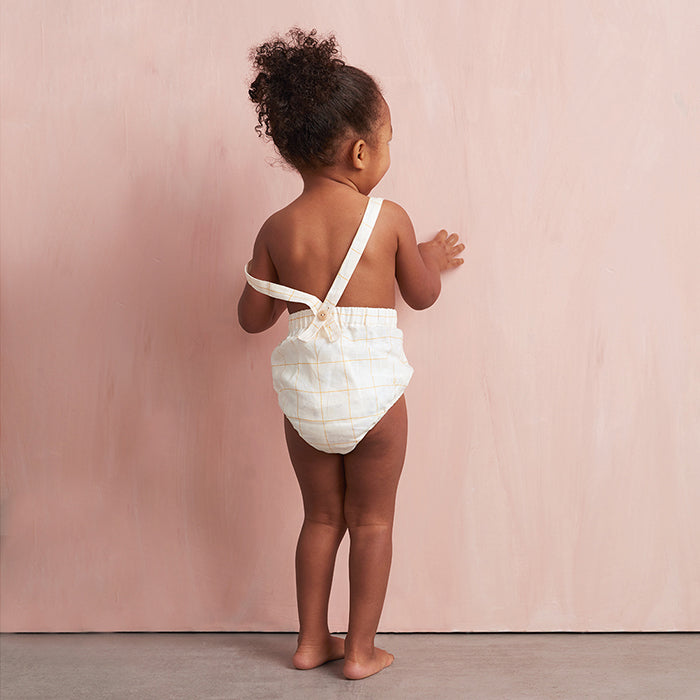 Standing baby girl from behind wearing Oeuf's short overalls.