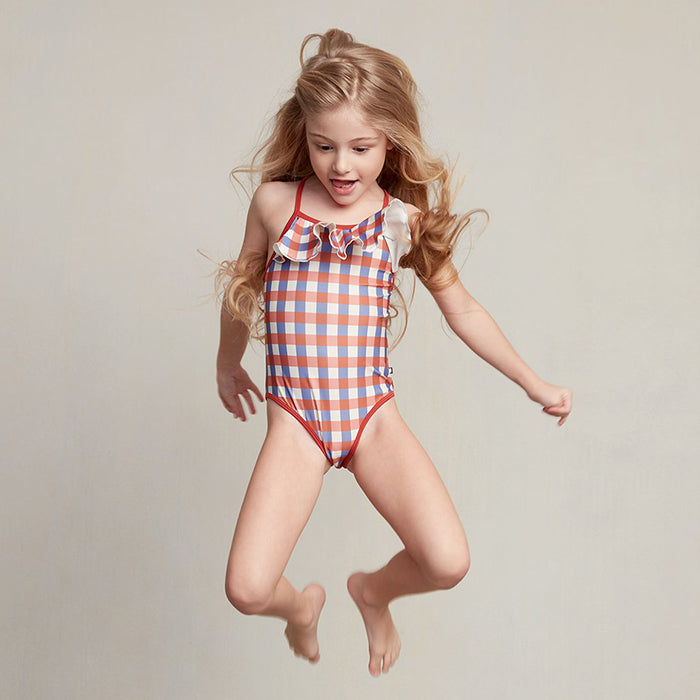 Jumping girl wearing a one-piece bathing suit.