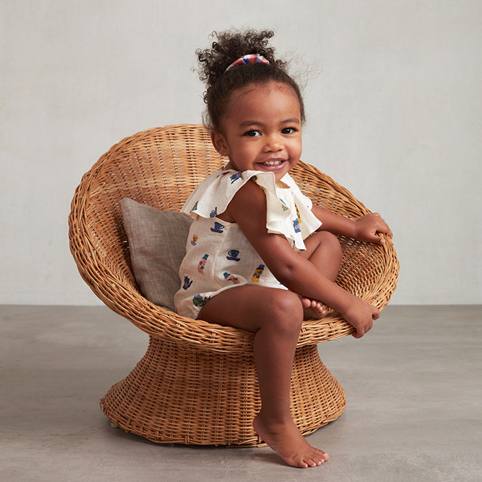 Toddler girl in a wicker chair wearing a romper.